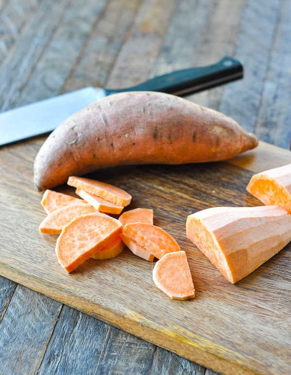 Chopped and peeled sweet potatoes on a cutting board