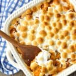 Overhead shot of sweet potato casserole with marshmallows on a wooden table