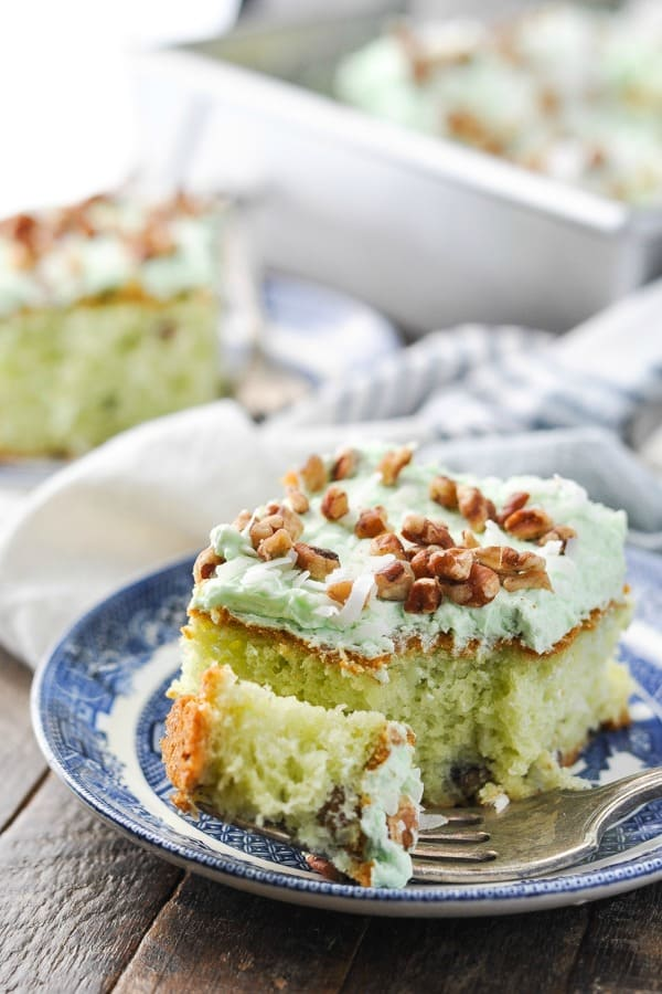 Close up front shot of a slice of pistachio pudding cake with coconut and pecans