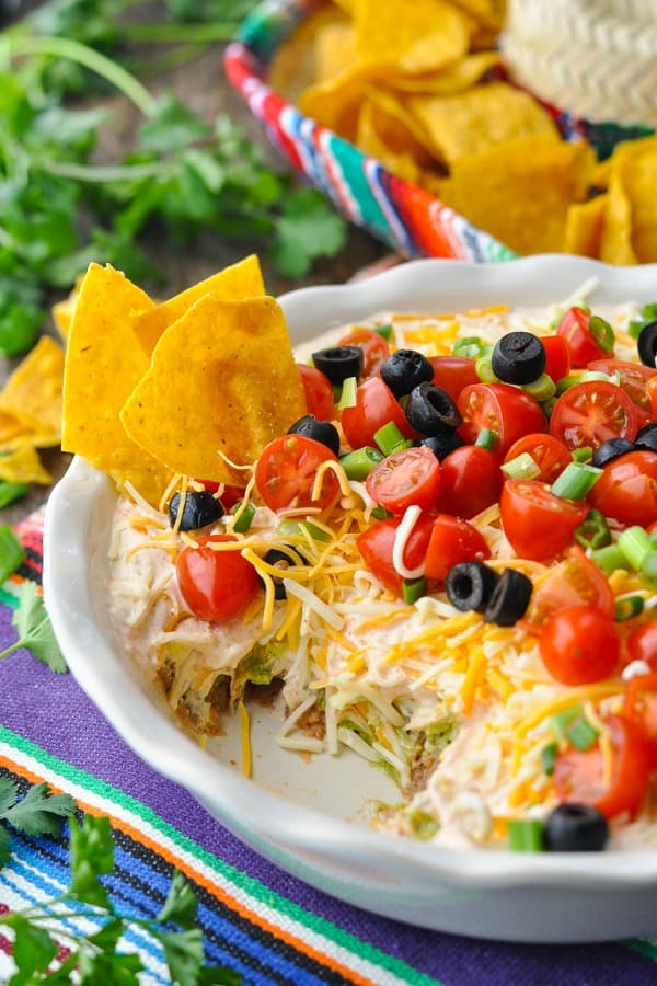 Front shot of Mexican 7 layer taco dip on a striped placemat