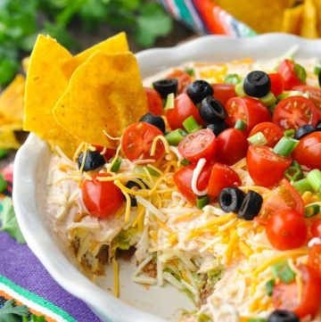 Front shot of 7 layer bean dip in a white dish with tortilla chips in it