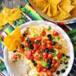 Overhead shot of 7 layer dip on a wooden surface served with tortilla chips