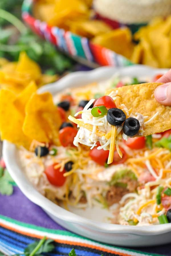 Close up shot of hand holding a tortilla chip with 7 layer bean dip on it