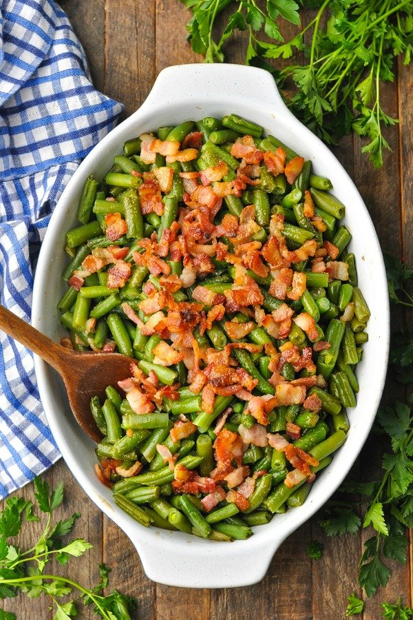 Overhead shot of Southern Style Green Beans in a baking dish with wooden serving spoon