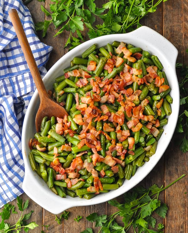 Overhead shot of green beans with bacon in a casserole dish on a wooden surface