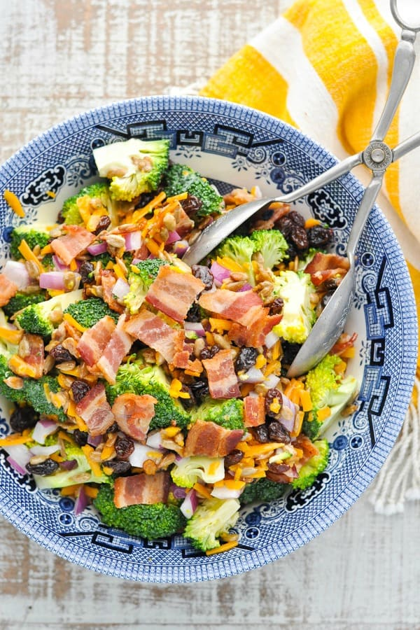 Close overhead shot of a bowl of broccoli salad with bacon and silver serving tongs