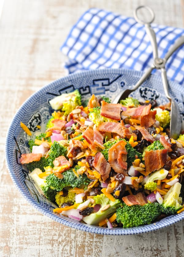 Close up front shot of broccoli salad with bacon in a blue and white bowl