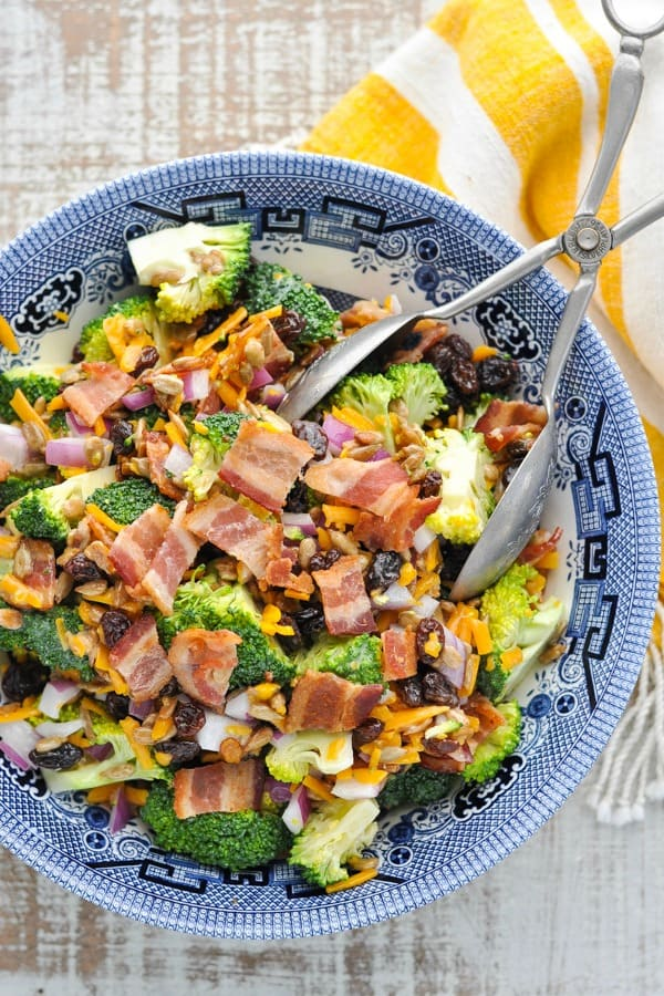 Overhead shot of broccoli salad with bacon in a blue and white serving bowl