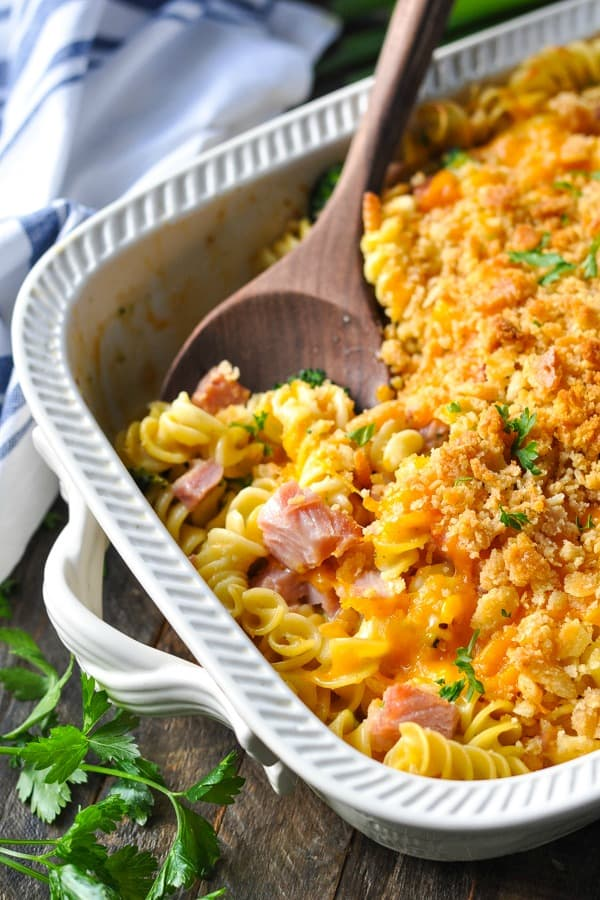 Close up side shot of ham and noodle casserole in a white baking dish