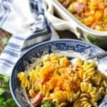 Front shot of ham casserole with pasta in a blue and white dinner dish with a fork