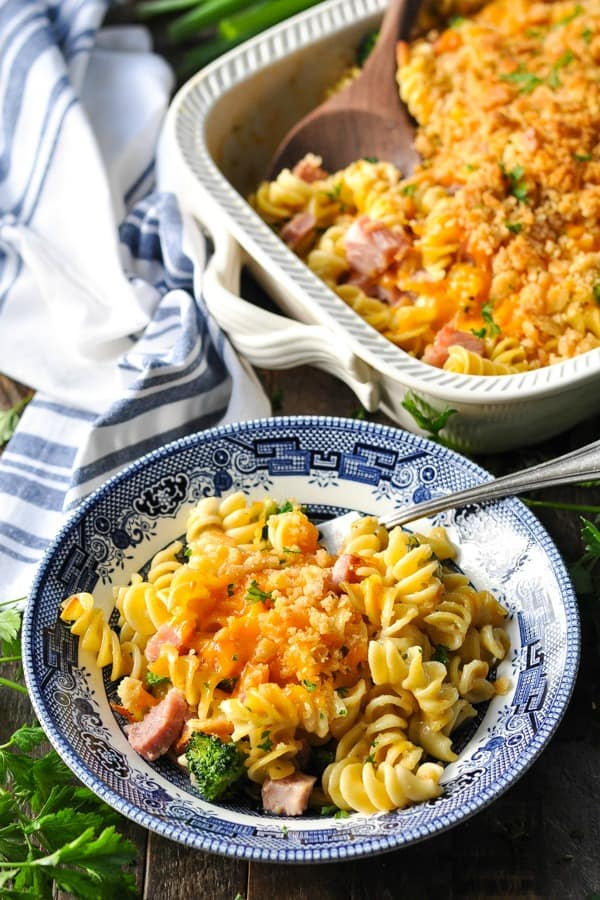 Bowl of ham casserole garnished with fresh parsley with a blue and white striped napkin nearby