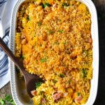 Overhead shot of ham cheese and broccoli casserole in a white baking dish on a wooden table