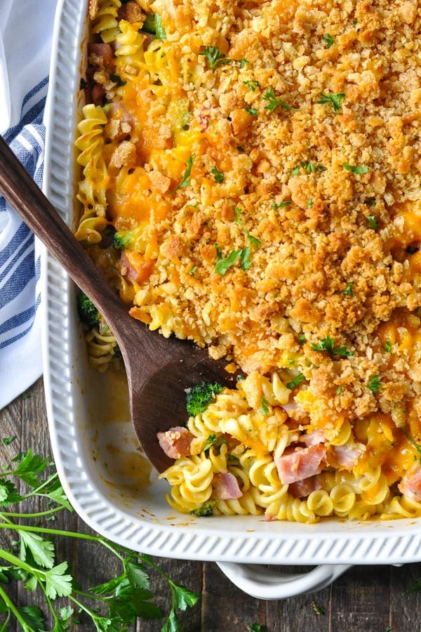 Close overhead shot of cheesy ham and noodle casserole in a white dish with wooden spoon