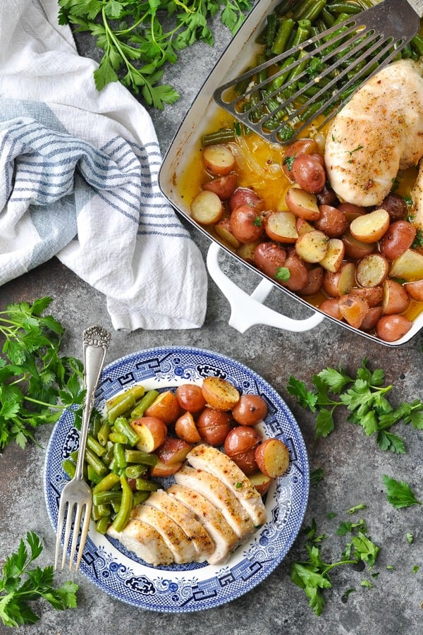 Overhead image of one pan chicken and potatoes with green beans on a gray table surface