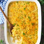 Overhead image of baked chicken and rice casserole with a wooden serving spoon
