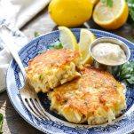 Two crab cakes on a plate with lemon wedges