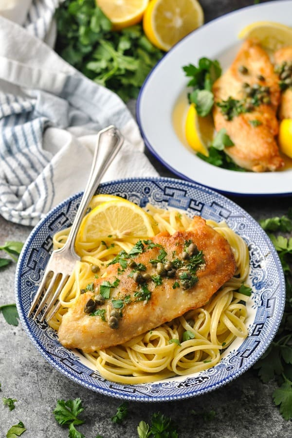 Front shot of a bowl of lemon chicken piccata with pasta and a fork