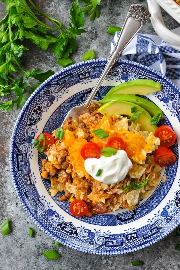 Close overhead shot of nacho casserole in a blue and white dish with sliced avocado on top