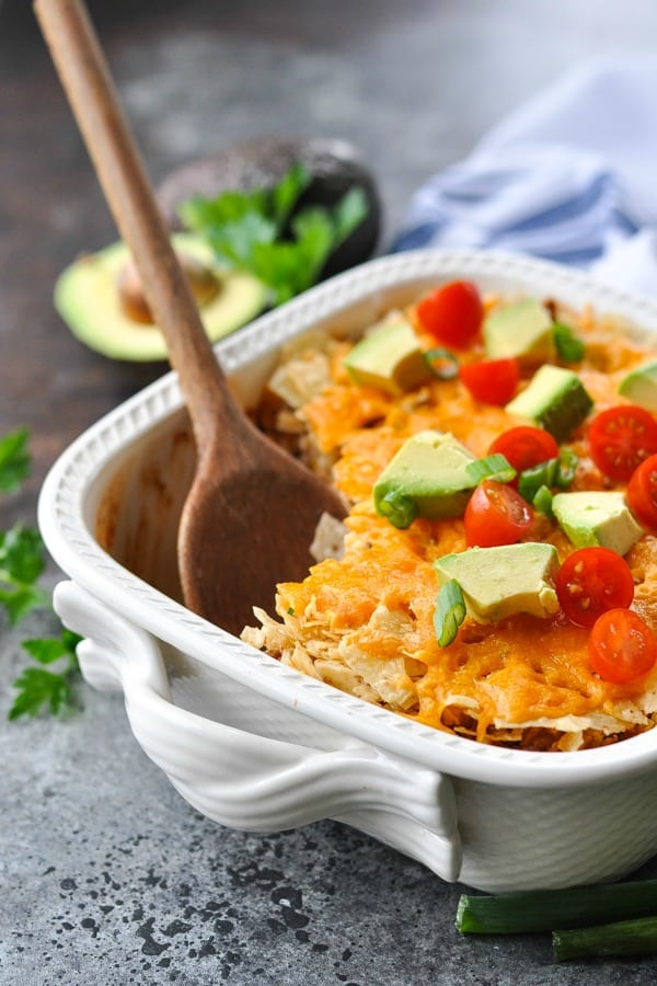 Wooden spoon in a nacho casserole with toppings