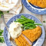 Overhead shot of breaded pork chops on a plate with green beans and mashed potatoes