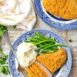 Oven Fried Pork Chops with green beans and mashed potatoes on a blue and white plate