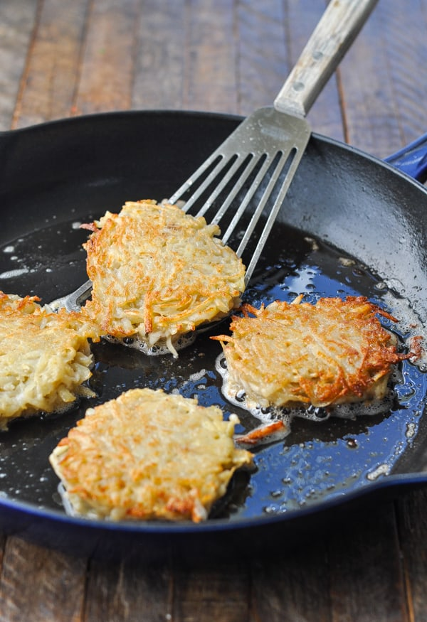 Process shot of frying potato pancakes recipe in a cast iron skillet
