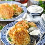 Image of potato pancakes on a blue and white plate on a wooden surface