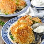 Close up front shot of potato pancakes on a blue and white plate with sour cream and applesauce