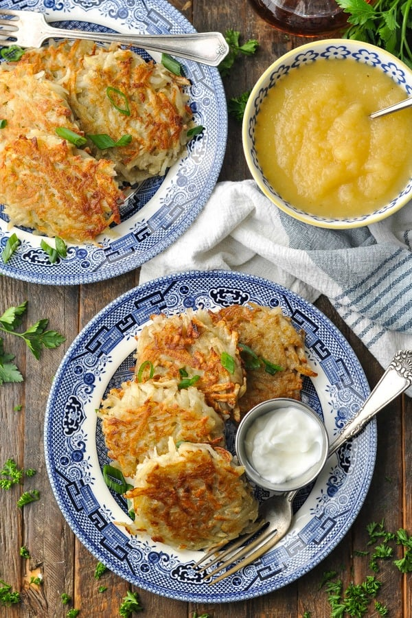 Overhead shot of two plates of potato pancakes on a wooden table