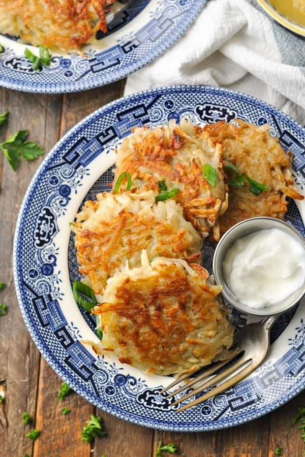 Close overhead shot of four potato pancakes on a blue and white plate surrounded by fresh parsley and garnished with chives