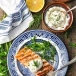 Overhead shot of grilled salmon fillet topped with a dollop of creamy yogurt dill sauce