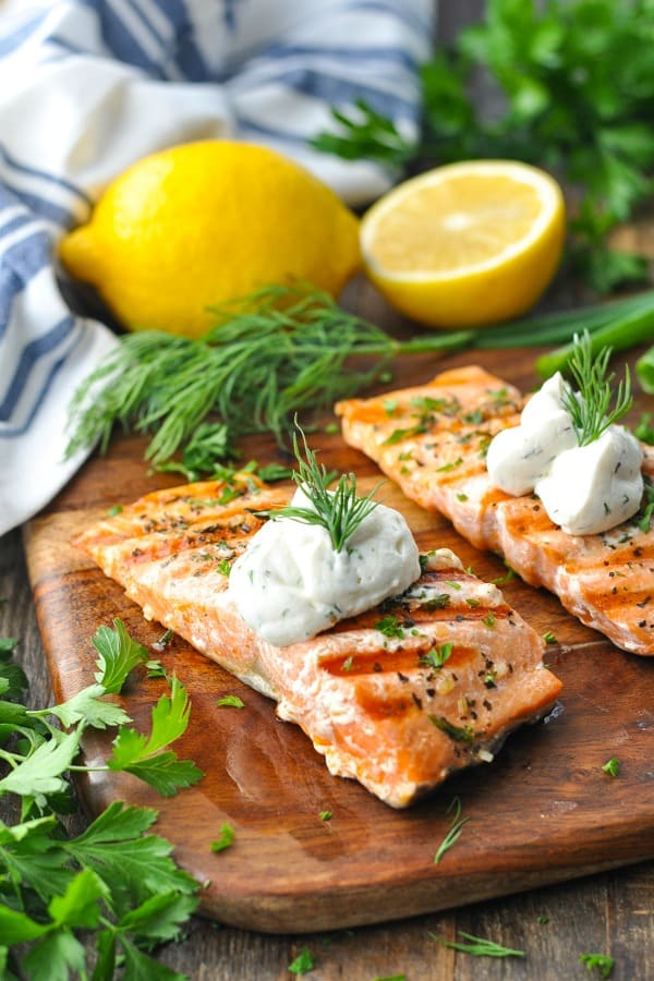 Grilled salmon fillets on a cutting board topped with creamy dill sauce
