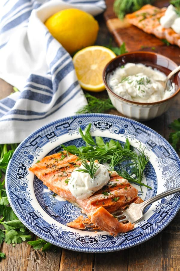 Salmon with dill sauce on a blue and white plate with blue and white striped napkin in the background