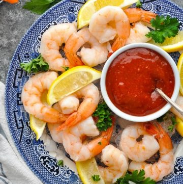 Close overhead shot of shrimp cocktail on a blue and white platter