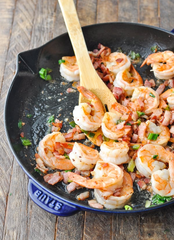 Shrimp cooked in a cast iron skillet with bacon and green onions