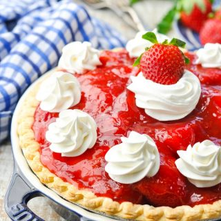 Fresh old fashioned strawberry pie recipe on a white wooden surface garnished with whipped cream
