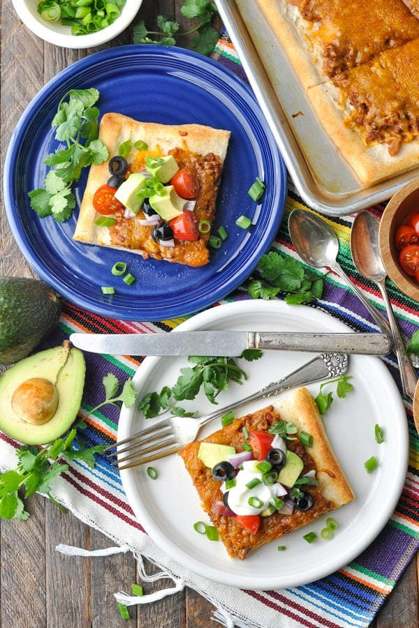 Overhead image of slices of Taco Pizza on blue and white plates
