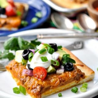 Front shot of a slice of Taco Pizza on a white plate with toppings