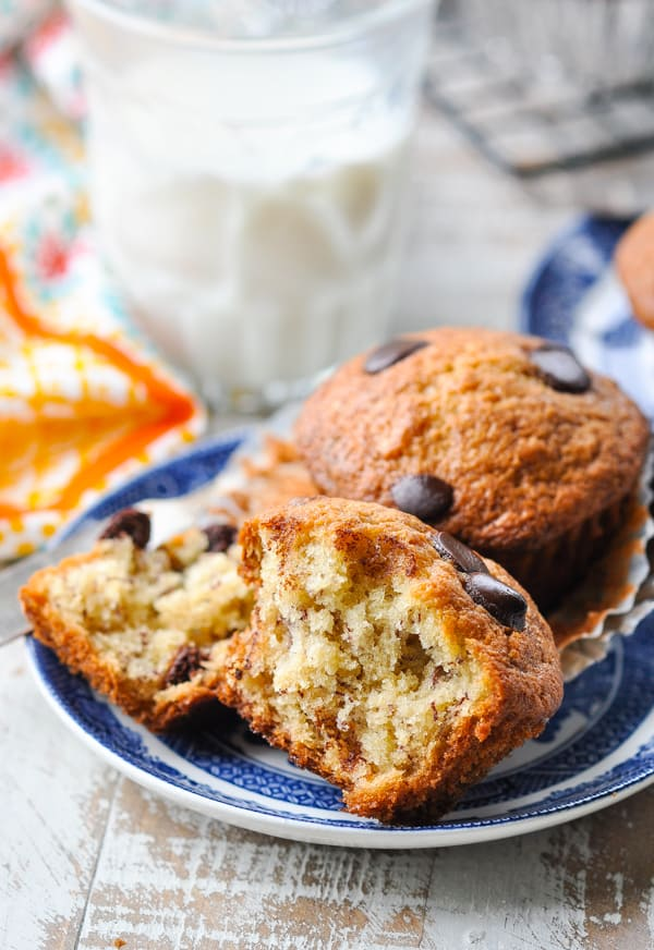 Two banana chocolate chip muffins on a plate with one cut in half to show the inside