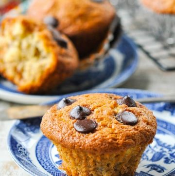 Close up front shot of banana chocolate chip muffin on a plate with more muffins in the background