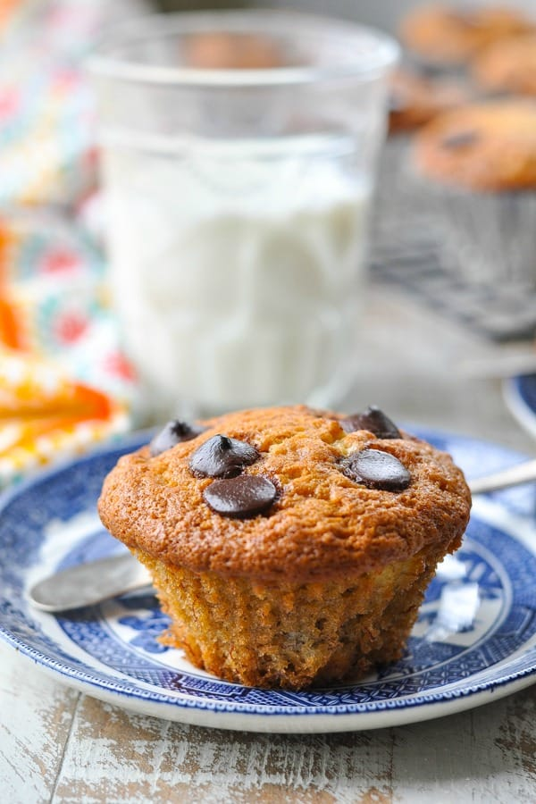Front shot of banana chocolate chip muffin on a blue and white plate with a glass of milk in the background
