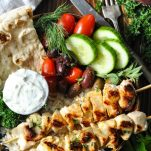 Close overhead shot of marinated and grill chicken souvlaki skewers with pita and yogurt sauce