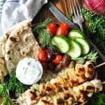 Chicken souvlaki in a bowl with fresh vegetables and tzatziki sauce and pita