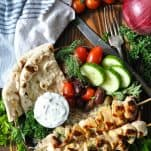 Overhead shot of chicken souvlaki pita on a wooden table with fresh vegetables and tzatziki