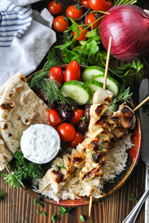 Overhead image of a bowl of healthy chicken souvlaki with tzatziki sauce and rice