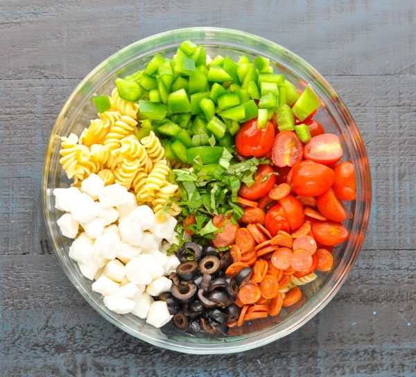 Ingredients for creamy pasta salad recipe in a large glass mixing bowl