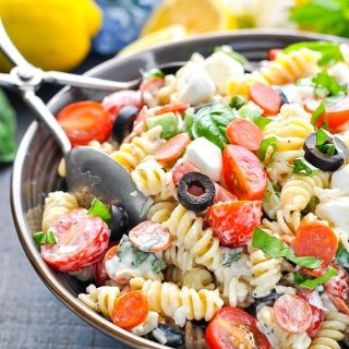 Front shot of a bowl of creamy pasta salad with serving tongs