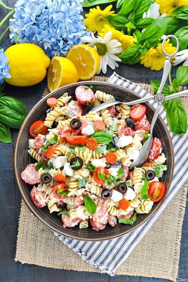 An easy creamy pasta salad recipe served in a large bowl on a blue and white striped napkin