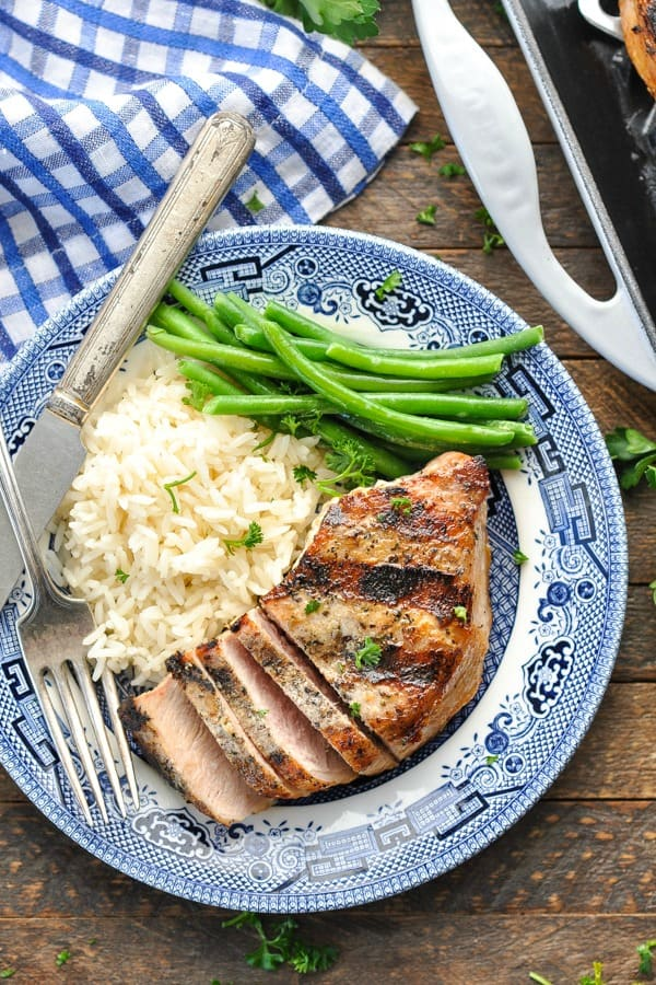 Close overhead shot of a sliced grilled pork chop on a blue and white serving plate