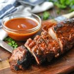 Grilled pork tenderloin on a wooden cutting board and basted with barbecue sauce